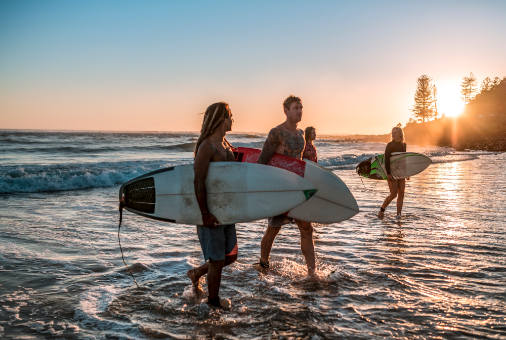 Friends Walking Along The Coast With Surfboards