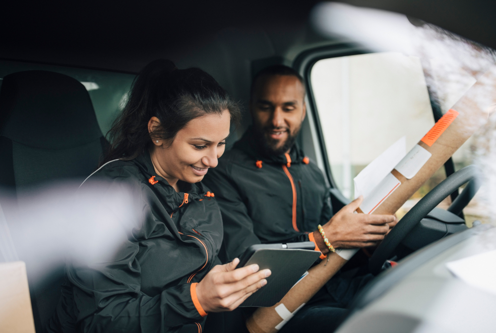 Smiling Workers Looking At Digital Tablet While Sitting In Delivery Van