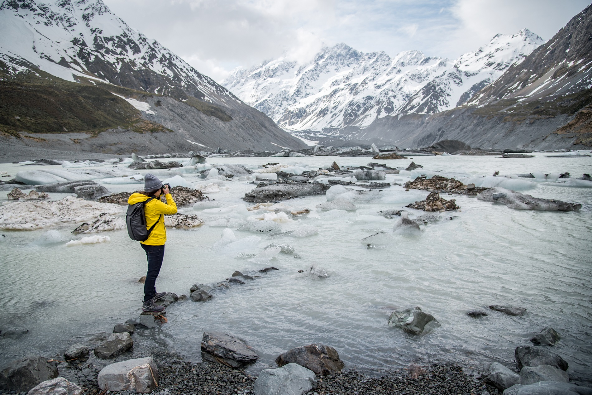 Young Asian Woman Taking Photos On Hooker Glacier In Aoraki / Mount Cook National Park, New Zealand