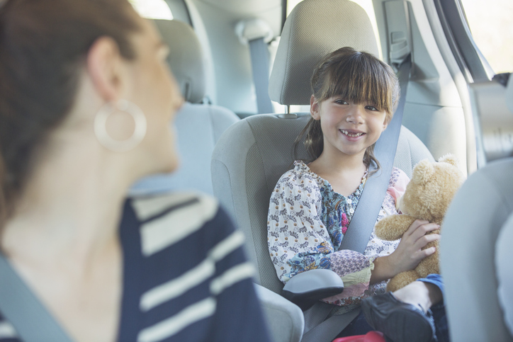 Mother Turning And Smiling At Daughter In Back Seat Of Car